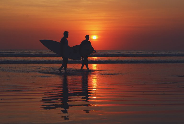 Two surfers walking on the Kuta beach with the sunrise in the background, Bali