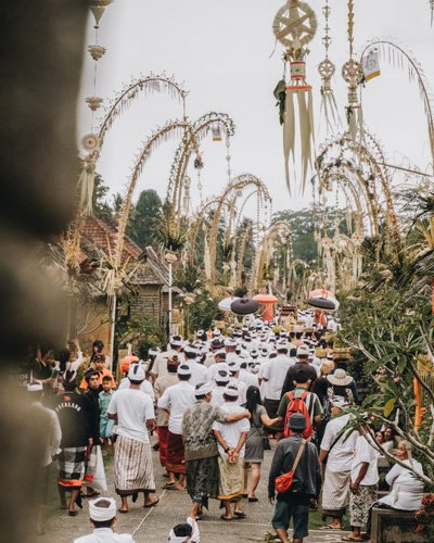 Several people walking through the streets decorated with Penjar during the Galungan and Kuningan festivities