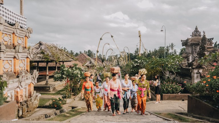 Several people carrying offerings on their heads in the traditional village of Penglipuran, Bali