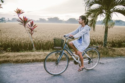 A girl is having a bicycle trip through the rice fields in Bali